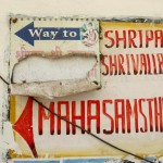 An unremarkable signpost at a wall to the ashram